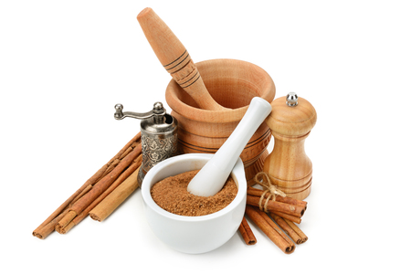 Cinnamon, mortar and pestle, hand grinder isolated on white