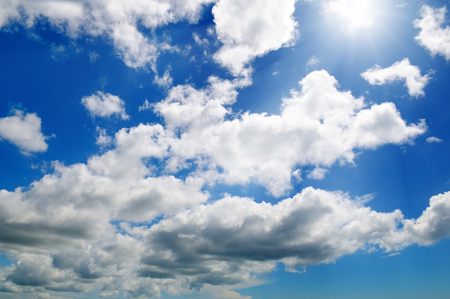 Bright sun on blue sky with white clouds.
