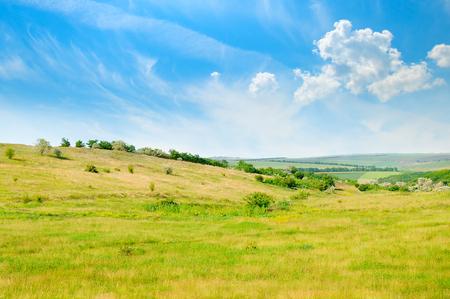Paisaje con campo montañoso y cielo azul. Paisaje agrícola.