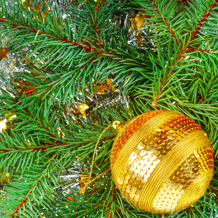 Christmas or New Year ornament. Bright golden ball on the background of a wreath of spruce twigs. Flat lay, top view.