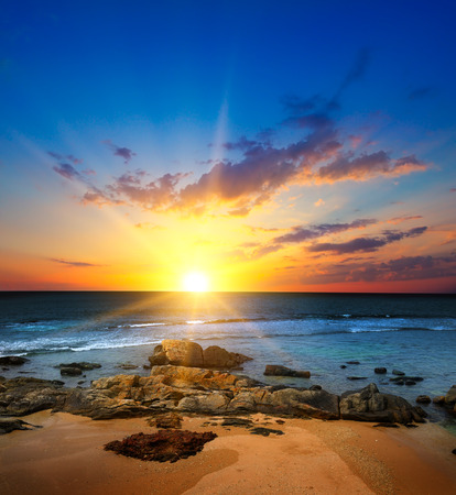 Picturesque seascape. Sunrise over the ocean, sandy beach with coral riffs.