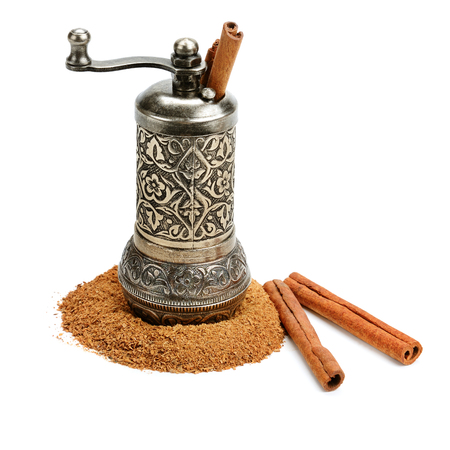 Cinnamon and manual grinder isolated on white background