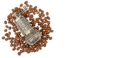 Manual coffee grinder and roasted coffee beans isolated on white background. Top view.