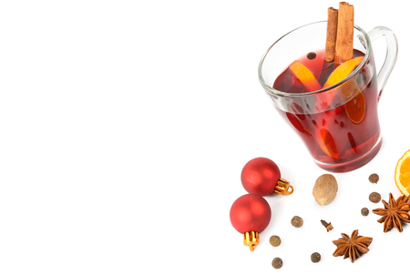 Hot red mulled wine isolated on white  with christmas spices, orange slice, anise and cinnamon sticks, close up.