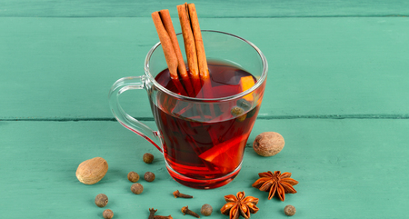 Hot red mulled wine on wooden  with spices, orange slice, anise and cinnamon sticks.