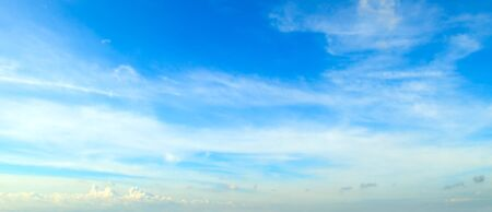 White fluffy clouds in the blue sky. Wide photo.