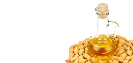 Peanuts and oil in bottle isolated on white background. Organic food. Free space for text. Wide photo.