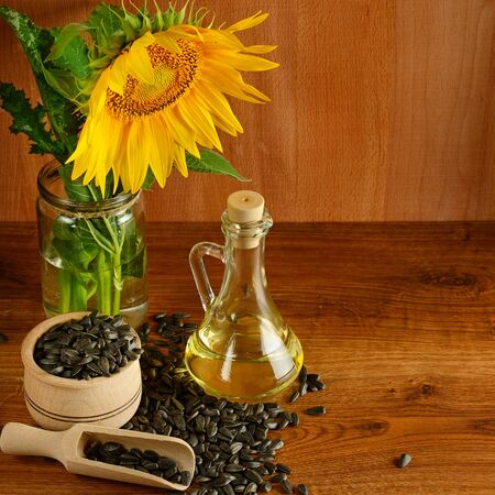Seeds, oil and sunflowers flower on a wooden background.