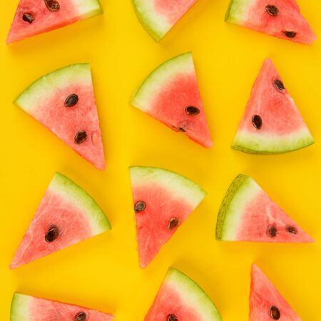 Sliced ripe juicy watermelon on a bright yellow background. Flat lay, top view.