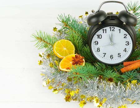 Christmas ornament. Watches, spruce branches, spices, slices of oranges on a white wooden background. Free space for text.
