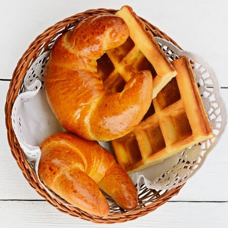 Appetizing croissants and waffles in a wicker basket on a white background. View from above.
