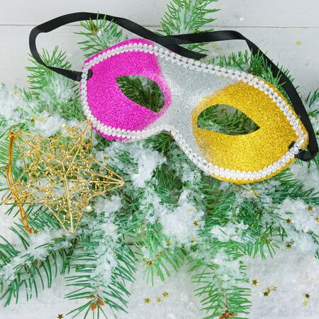 Christmas ornament. A wreath of fir branches, a mask and a decorative star on a white wooden background. 스톡 콘텐츠