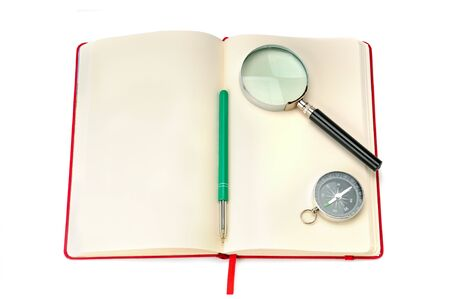 Open notebook with compass, magnifying glass and free space for text. Items are isolated on a white background.