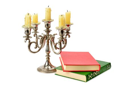 Old candlestick with candles and book isolated on white background.