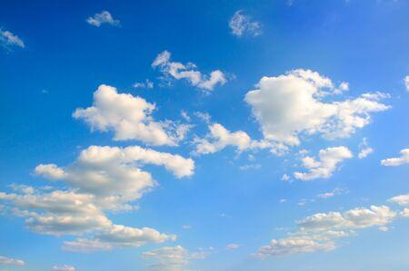 White cumulus clouds in the blue sky .