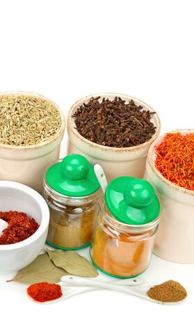 Composition with different spices and mortar on white background.