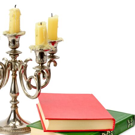 Old candlestick with candles and book isolated on white background. Free space for text.