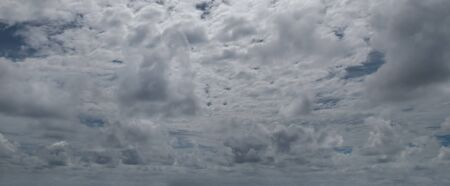 Sky with gray cumulus clouds. Dramatic cloud cover. Wide photo .