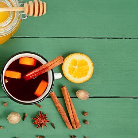 Mulled wine in white rustic mugs with spices and citrus fruit. Free space for text. Standard-Bild