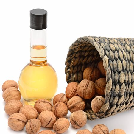 Walnut oil and nuts isolated on white background.