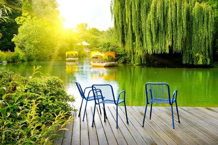 Lake, pleasure boats and garden furniture on a wooden pier. Standard-Bild