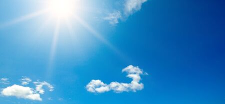 Couds in the blue sky. Bright midday sun illuminates the space. Wide photo . Standard-Bild