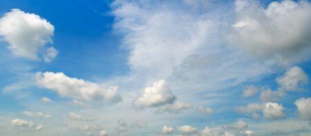 White cumulus clouds in the blue sky . Wide photo