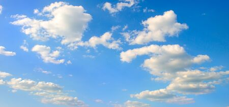 White cumulus clouds in the blue sky . Wide photo