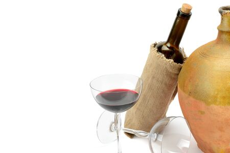 Glass with red wine, a bottle and a vintage jug isolated on white background. Free space for text.