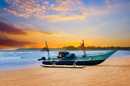 Beautiful seascape. Against the background of the sunset sky and the ocean, an old fishing boat. Sri Lanka Foto de archivo