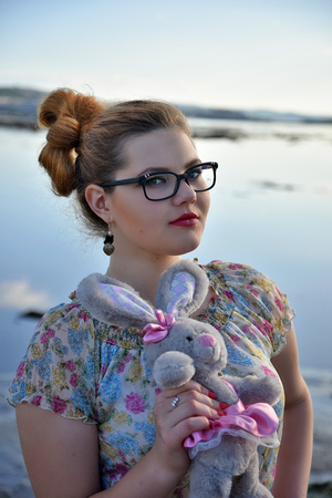 new age: Girl with stuffed bunny at lake