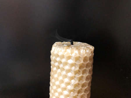 fading candle with honeycomb texture on black background Stock Photo