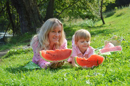 Little boy with mother on the river bank eat watermelon