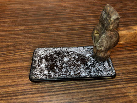 Mobile phone with broken glass on a dark wooden background. Hammer beating on the phone
