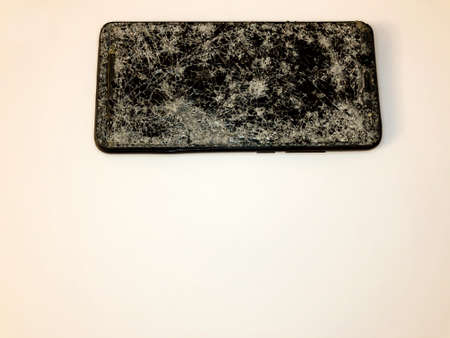 Broken glass mobile phone on a white background Фото со стока