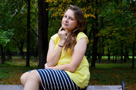 Woman with dark hair in a yellow T-shirt sits on a wooden bench Фото со стока