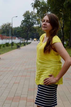 Woman with dark hair in a yellow T-shirt Фото со стока