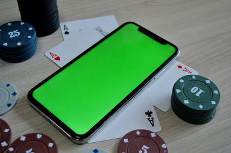 Poker background - chips, cards and phone with a green screen