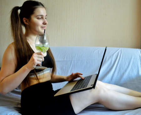 Young beautiful girl with dark hair with a laptop and a glass on the sofa.