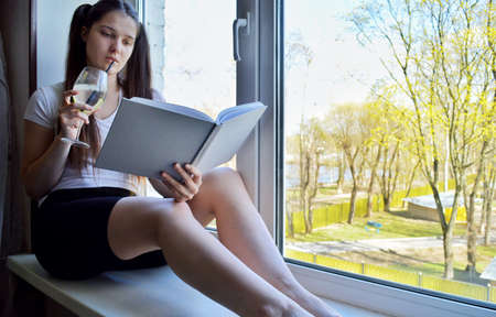 Young beautiful girl with dark hair with a gray paper book and a glass on the windowsill