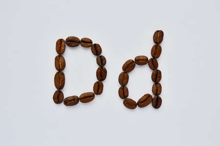 letters d made of coffee beans on the white background.