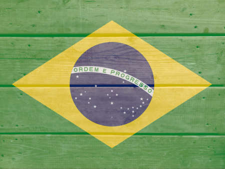 Brazil flag painted on wood plank background. Brushed natural light knotted wooden board texture. Wooden texture background flag of Brazil