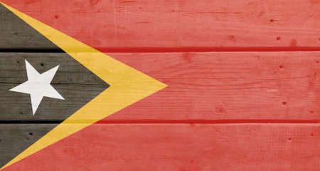 East Timor flag painted on wood plank background. Brushed natural light knotted wooden board texture. Wooden texture background flag of East Timor