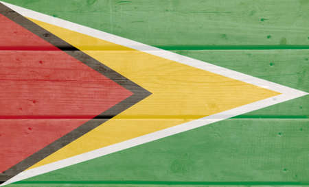 Guyana flag painted on wood plank background. Brushed natural light knotted wooden board texture. Wooden texture background flag of Guyana