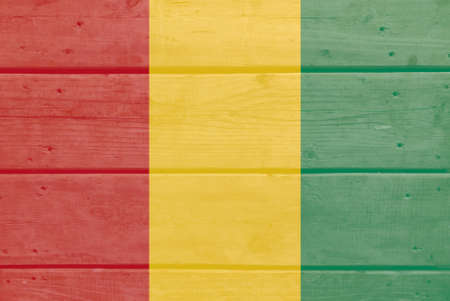 Guinea flag painted on wood plank background. Brushed natural light knotted wooden board texture. Wooden texture background flag of Guinea