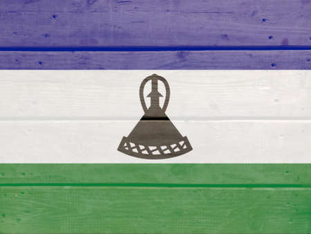 Lesotho flag painted on wood plank background. Brushed natural light knotted wooden board texture. Wooden texture background flag of Lesotho