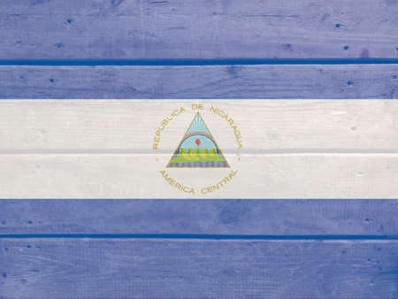 Nicaragua flag painted on wood plank background. Brushed natural light knotted wooden board texture. Wooden texture background flag of Nicaragua