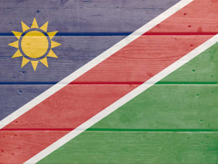 Namibia flag painted on wood plank background. Brushed natural light knotted wooden board texture. Wooden texture background flag of Namibia