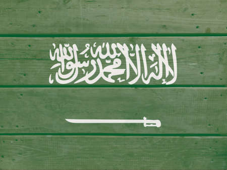Saudi Arabia flag painted on wood plank background. Brushed natural light knotted wooden board texture. Wooden texture background flag of Saudi Arabia