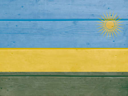 Rwanda flag painted on wood plank background. Brushed natural light knotted wooden board texture. Wooden texture background flag of Rwanda